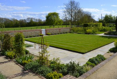Square lawn in back garden surrounded by paving and shrubs