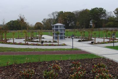 Landscaped area with paved circle path and lawn