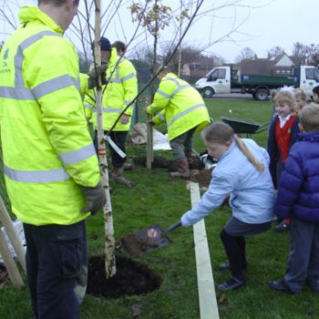 Community tree planting with child planting tree