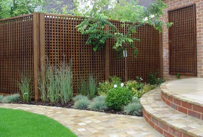 Fencing behind garden shrubs and paving