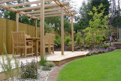 Wooden table under wooden pergola on decking by lawn