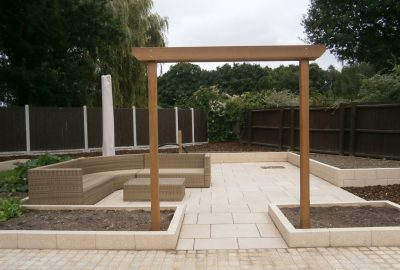 Paved area in garden with wooden entrance