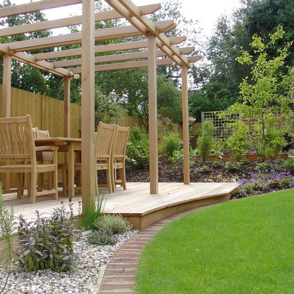 Wooden pergola in garden with wooden table and chairs underneath