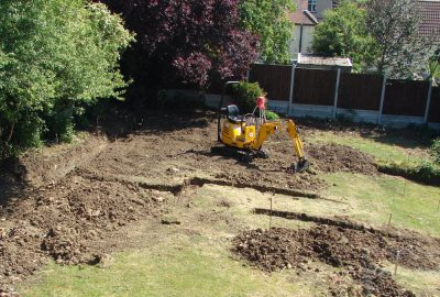 Site clearance with digger digging trenches in lawn