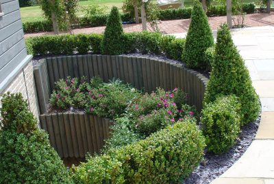 Soft landscaping with bushes and wooden entrances